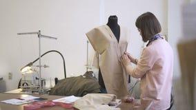 Ο νέος σχεδιαστής μόδας συνεχίζει εργασίας, διαμορφώνει τα ενδύματα σύμφωνα με το μανεκέν με το ύφασμα, που στέκεται στο ράψιμο τ απόθεμα βίντεο