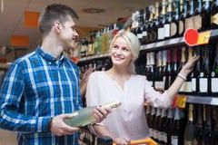 Ο νέος σύζυγος αγοράζει το κρασί στο κατάστημα Στοκ Εικόνα