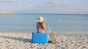 Ο νέος ταξιδιώτης γυναικών κάθεται στην παραλία με μια βαλίτσα απόθεμα βίντεο