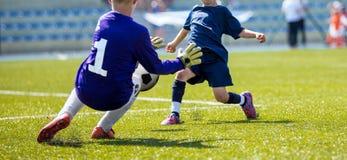 Ο νέος τερματοφύλακας ποδοσφαίρου σώζει Άλματα αγοριών για να πιάσει τη σφαίρα ποδοσφαίρου Στοκ Φωτογραφίες