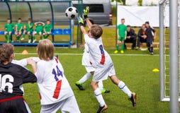 Ο νέος τερματοφύλακας ποδοσφαίρου σώζει Αγόρι που πηδά και που πιάνει τη σφαίρα ποδοσφαίρου Στοκ Φωτογραφία
