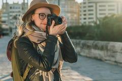 Ο νέος τουρίστας γυναικών, φωτογράφος, hipster κορίτσι έντυσε στο καπέλο και eyeglasses, στάσεις στην οδό πόλεων και παίρνει τη φ Στοκ εικόνα με δικαίωμα ελεύθερης χρήσης
