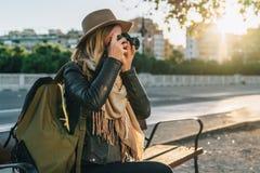 Ο νέος τουρίστας γυναικών, φωτογράφος, hipster κορίτσι κάθεται στον πάγκο στην οδό πόλεων και παίρνει τη φωτογραφία Διακοπές, ταξ Στοκ Φωτογραφία