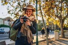 Ο νέος τουρίστας γυναικών, φωτογράφος, hipster κορίτσι κάθεται στον πάγκο στην οδό πόλεων και παίρνει τη φωτογραφία Διακοπές, ταξ Στοκ Εικόνες