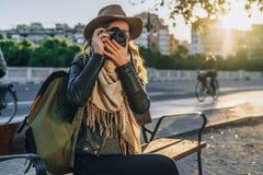 Ο νέος τουρίστας γυναικών, φωτογράφος, hipster κορίτσι κάθεται στον πάγκο στην οδό πόλεων και παίρνει τη φωτογραφία Διακοπές, ταξ Στοκ Φωτογραφίες