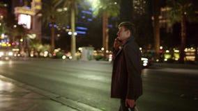 Ο νέος τουρίστας περπατά σε Vegas τη νύχτα και μιλά πέρα από το κινητό τηλέφωνο του απόθεμα βίντεο