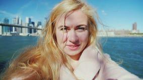 Ο νέος τουρίστας σε ένα ρόδινο παλτό λαμβάνεται στο βίντεο, που κρατά τη κάμερα στα χέρια του Ενάντια στο σκηνικό απόθεμα βίντεο
