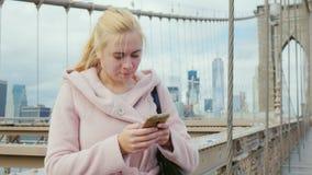 Ο νέος τουρίστας σε ένα ρόδινο παλτό χρησιμοποιεί ένα smartphone απόθεμα βίντεο