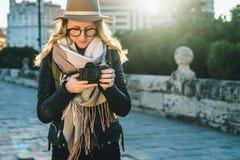 Ο νέος τουρίστας, ο φωτογράφος, hipster το κορίτσι γυναικών στις στάσεις καπέλων στην οδό πόλεων και χρησιμοποιούν τη κάμερα, φαί Στοκ Εικόνες