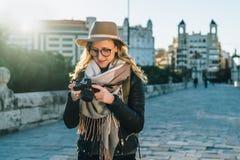 Ο νέος τουρίστας, ο φωτογράφος, hipster το κορίτσι γυναικών στις στάσεις καπέλων στην οδό πόλεων και χρησιμοποιούν τη κάμερα, φαί Στοκ εικόνες με δικαίωμα ελεύθερης χρήσης