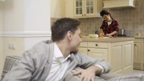 Ο νέος τύπος γυρίζει στη φίλη του που μαγείρεμα ` s στην κουζίνα απόθεμα βίντεο
