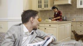 Ο νέος τύπος εξετάζει μέσω των εγγράφων και των στροφών στη φίλη την κουζίνα απόθεμα βίντεο