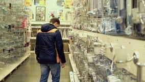 Ο νέος τύπος εξετάζει τα εξαρτήματα λουτρών στο κατάστημα οικοδομικών υλικών φιλμ μικρού μήκους
