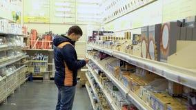 Ο νέος τύπος εξετάζει τα ηλεκτρικά αγαθά, λαμπτήρες, σε ένα κατάστημα οικοδομικών υλικών απόθεμα βίντεο