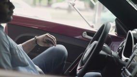 Ο νέος τύπος επιθεωρεί μέσα στο σύγχρονο αυτοκίνητο στην αίθουσα εκθέσεως αυτοκινήτων φιλμ μικρού μήκους
