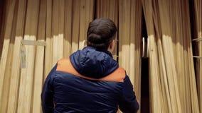 Ο νέος τύπος επιλέγει τις ξύλινες ακτίνες σε ένα κατάστημα οικοδομικών υλικών απόθεμα βίντεο