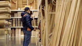 Ο νέος τύπος επιλέγει τις ξύλινες ακτίνες στο κατάστημα οικοδομικών υλικών απόθεμα βίντεο