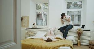 Ο νέος τύπος κάνει τις εικόνες για τη φίλη του στην άνετη κρεβατοκάμαρά τους, καθορίζει στο κρεβάτι και φορά ένα χαριτωμένο ροζ απόθεμα βίντεο
