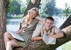 Τους εφήβους που διαβάζονται τα βιβλία υπαίθρια στην ηλιόλουστη ημέρα Στοκ Εικόνα