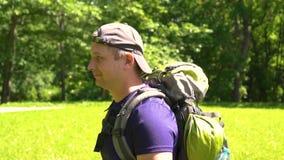 Ο νέος τύπος με ένα σακίδιο πλάτης περπατά στο πάρκο, ημέρα φιλμ μικρού μήκους