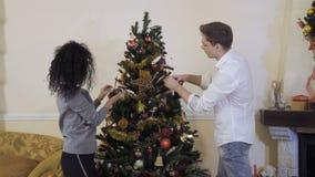 Ο νέος τύπος με τη φίλη διακοσμεί το χριστουγεννιάτικο δέντρο απόθεμα βίντεο