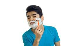 Ο νέος τύπος με τον αφρό στο πρόσωπό του ξυρίζει την κινηματογράφηση σε πρώτο πλάνο μηχανών γενειάδων του Στοκ φωτογραφία με δικαίωμα ελεύθερης χρήσης