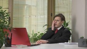 Ο νέος τύπος σε ένα κοστούμι κάθεται στο γραφείο, που λειτουργεί σε ένα lap-top, που κουράζεται, πέφτοντας κοιμισμένος, τρυπημένο φιλμ μικρού μήκους
