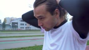 Ο νέος τύπος σε μια αθλητική μπλούζα στον όμορφο τύπο σταδίων με τη σκοτεινή τρίχα προετοιμάζεται για τον αθλητικό τύπο workout υ απόθεμα βίντεο