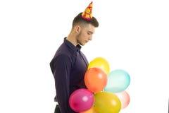 Ο νέος τύπος στέκεται στο στούντιο και κρατά πολλά μπαλόνια στοκ φωτογραφία