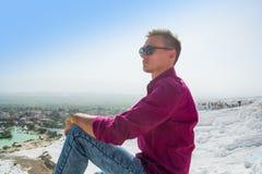 Ο νέος τύπος στα γυαλιά ηλίου κάθεται και θαυμάζει την άποψη Pamukkale, Στοκ Φωτογραφία