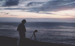 Ο νέος τύπος hipster με μακρυμάλλη παίρνει μια εικόνα στη φωτογραφία ενός ηλιοβασιλέματος θάλασσας τη νύχτα σε ένα υπόβαθρο ηλιοβ στοκ φωτογραφίες