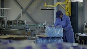 Ο νέος υπάλληλος βάζει τα μπουκάλια του νερού στο εργοστάσιο εργαστηρίων απόθεμα βίντεο