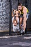 Ο νέος φίλαθλος πατέρας εκπαιδεύει το μικρό γιο με τα γυμναστικά δαχτυλίδια ενάντια στο τουβλότοιχο στη διαγώνια κατάλληλη γυμνασ Στοκ Φωτογραφία