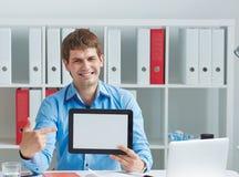 Ο νέος χαμογελώντας αρσενικός επιχειρηματίας παρουσιάζει κενή οθόνη της συνεδρίασης PC ταμπλετών στο γραφείο Επιχείρηση, αγορά αν Στοκ εικόνα με δικαίωμα ελεύθερης χρήσης
