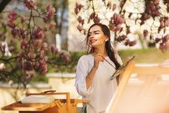 Ο νέος χαμογελώντας καλλιτέχνης γυναικών brunette χρωματίζει μια εικόνα στην οδό, κοντά σε ένα όμορφο δέντρο του magnolia στοκ φωτογραφία με δικαίωμα ελεύθερης χρήσης