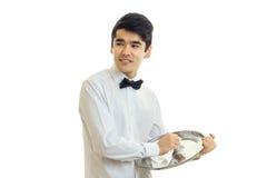 Ο νέος χαριτωμένος σερβιτόρος φαίνεται λοξά χαμόγελα και σκουπίζει την πετσέτα δίσκων Στοκ Εικόνα