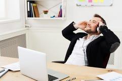 Ο νέος χαλαρωμένος επιχειρηματίας ακούει μουσική στο σύγχρονο άσπρο γραφείο Στοκ φωτογραφία με δικαίωμα ελεύθερης χρήσης