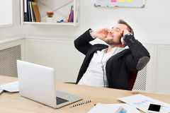 Ο νέος χαλαρωμένος επιχειρηματίας ακούει μουσική στο σύγχρονο άσπρο γραφείο Στοκ Φωτογραφίες