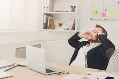 Ο νέος χαλαρωμένος επιχειρηματίας ακούει μουσική στο σύγχρονο άσπρο γραφείο Στοκ εικόνα με δικαίωμα ελεύθερης χρήσης