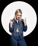 Ο νέος χούλιγκαν στα τζιν και ένα σακάκι τζιν παρουσιάζει διαφορετικά σημάδια με τα δάχτυλά της στοκ εικόνα με δικαίωμα ελεύθερης χρήσης