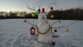 Ο νέος χρονικός χιονάνθρωπος Χριστουγέννων έτους στον τομέα με τα κεριά και το βράδυ καλύπτει, χρονικό σφάλμα 4K απόθεμα βίντεο