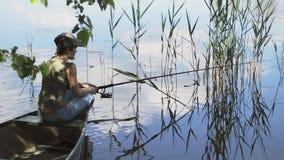 Ο νέος ψαράς γυναικών αλιεύει στη δασική λίμνη, κρατώντας τις συστροφές ράβδων αλιείας η σπείρα φιλμ μικρού μήκους