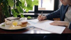 Ο νέος όμορφος επιχειρηματίας εργάζεται στο πρόγραμμα, καθμένος στον πίνακα στον καφέ φιλμ μικρού μήκους