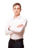 Ο νέος όμορφος επιχειρηματίας στο άσπρο πουκάμισο στέκεται κατ' ευθείαν και διασχίζει τα χέρια του, πορτρέτο που απομονώνεται στο Στοκ Εικόνα