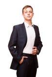 Ο νέος όμορφος επιχειρηματίας στο μαύρο κοστούμι στέκεται κατ' ευθείαν και η τοποθέτηση δικών του παραδίδει τις τσέπες, πορτρέτο  Στοκ Φωτογραφία