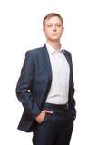 Ο νέος όμορφος επιχειρηματίας στο μαύρο κοστούμι στέκεται κατ' ευθείαν και η τοποθέτηση δικών του παραδίδει τις τσέπες, πορτρέτο  Στοκ εικόνα με δικαίωμα ελεύθερης χρήσης