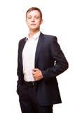 Ο νέος όμορφος επιχειρηματίας στο μαύρο κοστούμι στέκεται κατ' ευθείαν και η τοποθέτηση δικών του παραδίδει τις τσέπες, πορτρέτο  Στοκ Εικόνα