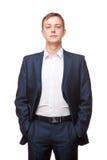 Ο νέος όμορφος επιχειρηματίας στο μαύρο κοστούμι στέκεται κατ' ευθείαν και η τοποθέτηση δικών του παραδίδει τις τσέπες, πορτρέτο  Στοκ Εικόνες
