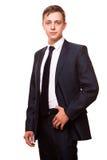 Ο νέος όμορφος επιχειρηματίας στο μαύρο κοστούμι στέκεται κατ' ευθείαν, πορτρέτο που απομονώνεται στο άσπρο υπόβαθρο Στοκ Φωτογραφίες