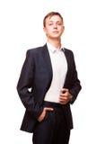 Ο νέος όμορφος επιχειρηματίας στο μαύρο κοστούμι στέκεται κατ' ευθείαν και η τοποθέτηση δικών του παραδίδει τις τσέπες, πορτρέτο  Στοκ Φωτογραφίες
